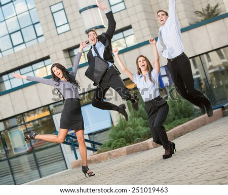 Group of young cheerful business people in front of office building, photographed at the moment of the jump.
