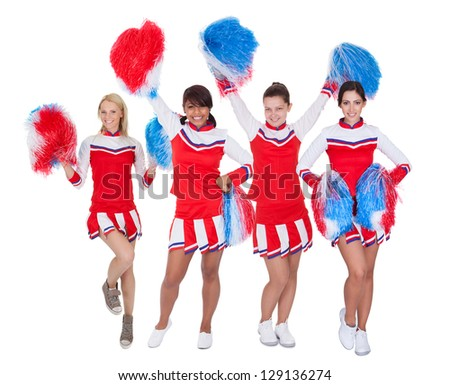 Group of young cheerleaders in red uniform. Isolated on white background - stock photo