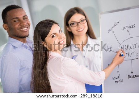 Group of young colleagues dressed casual standing together in modern office and smiling to camera. - stock photo