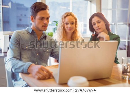 Group of young colleagues using laptop at the office