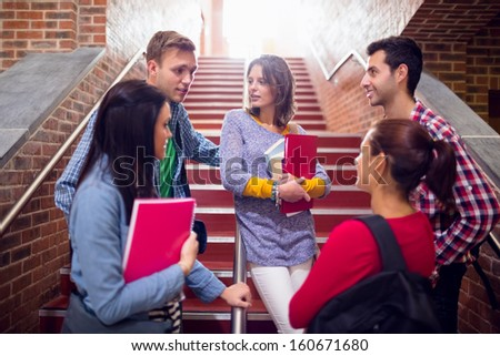 Group of young college students conversing on stairs in the college