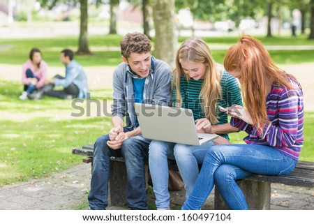 Group of young college students using laptop in the park - stock photo
