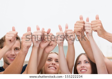 Group of young diverse business people giving a thumbs up standing with their arms raised in the air to indicate their success and approval - stock photo