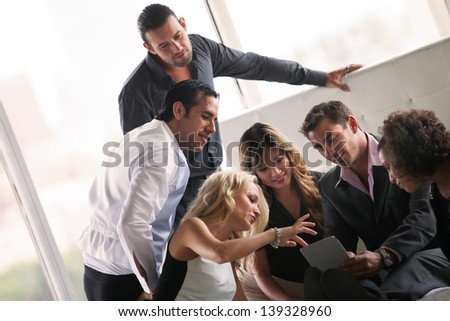 Group of young diverse ethnicity people getting together after a party looking at pictures on a  touch pad - stock photo