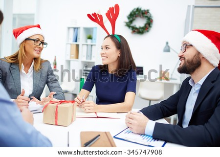 Group of young employees interacting at meeting on Christmas - stock photo