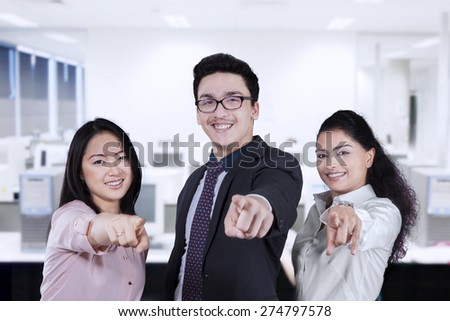 Group of young entrepreneurs smiling and pointing at camera in the workplace - stock photo
