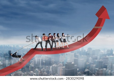 Group of young entrepreneurs tries to climb and pulling a financial graph upwards - stock photo