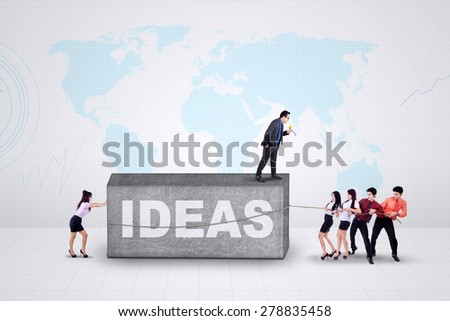 Group of young entrepreneurs try to move a stone with a text of ideas - stock photo