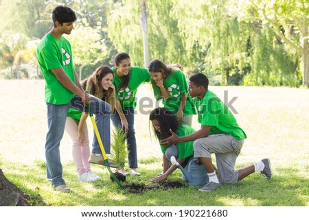 Group of young environmentalists planting in park - stock photo