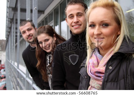 Group of young European students looking happy outdoors in a row - stock photo