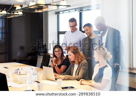 Group of young executives in conference room gathered together looking at laptop - stock photo