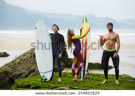 Group of young fancy people having fun while waiting surfing waves standing on the beach, surf camp holidays with international people - stock photo