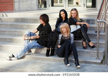Group of young fashion people sitting on the steps - stock photo