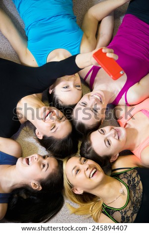 Group of young female friends lying on the floor taking picture, laughing, taking picture, selfie, self-portrait on smartphone view from above