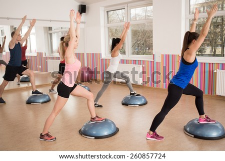 Group of young fit people exercising with bosu in fitness club - stock photo
