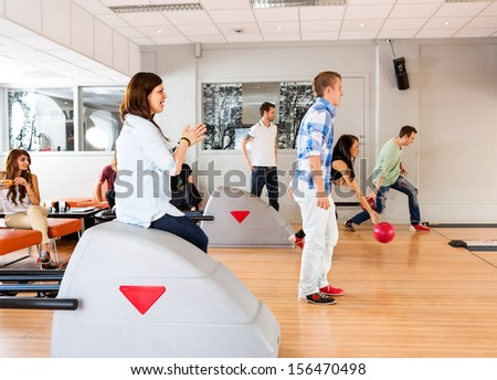 Group of young friends bowling together in club