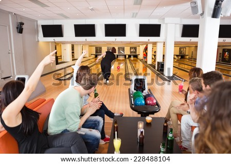 Group of young friends cheering woman bowling in club - stock photo