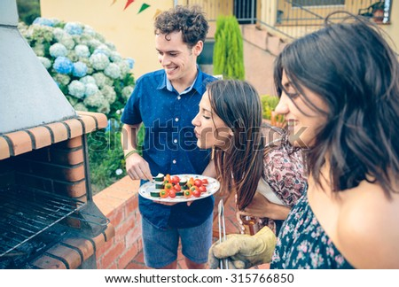 Group of young friends cooking vegetable skewers and having fun in a outdoors summer barbecue