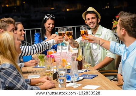 Group of young friends drinking beer outdoors terrace night out