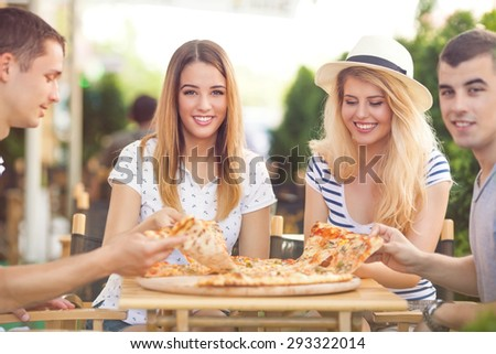Group of young friends eating pizza in a outdoor cafe - stock photo