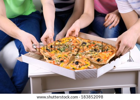Group of young friends eating pizza in living-room on sofa - stock photo