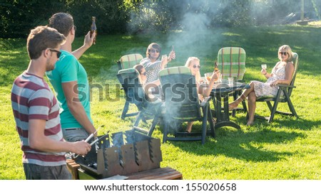 Group of young friends enjoying barbecue in a garden on a sunny afternoon - stock photo