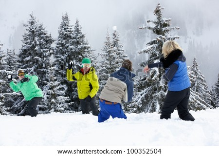Group Of Young Friends Having Snowball Fight On Ski Holiday In Mountains - stock photo