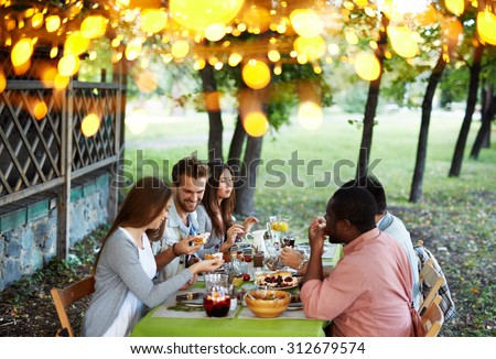 Group of young friends having traditional dinner on Thanksgiving Day - stock photo