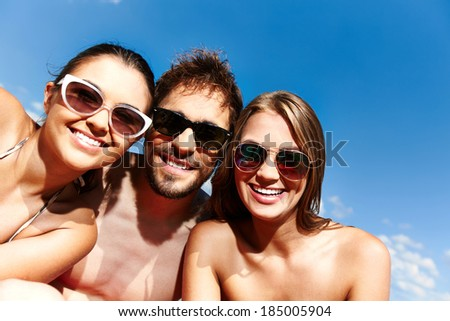 Group of young friends in sunglasses looking at camera against blue sky - stock photo