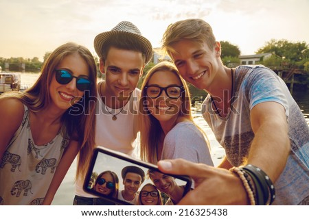 Group Of Young Friends Near River Taking Selfie Using Digital Tablet