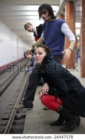 Group of young friends on edge of platform of subway station - stock photo