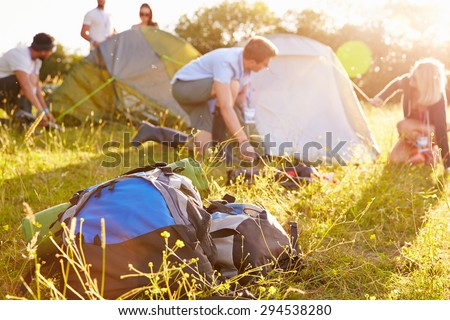 Group Of Young Friends Pitching Tents On Camping Holiday - stock photo