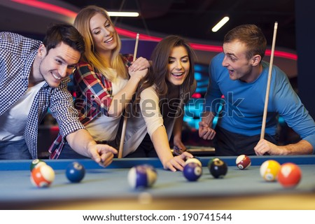 Group of young friends playing billiard - stock photo