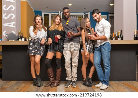 Group of young friends portrait having fun while drinking a cocktail in a bar. - stock photo