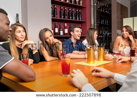 Group of young friends portrait having fun while having dinner in a restaurant.  - stock photo