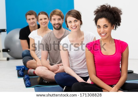 Group of young friends practicing yoga at the gym sitting cross legged on the floor in the lotus position smiling happily at the camera - stock photo