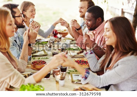 Group of young friends praying at Thanksgiving table - stock photo