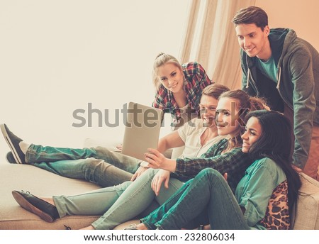 Group of young friends taking selfie in home interior  - stock photo