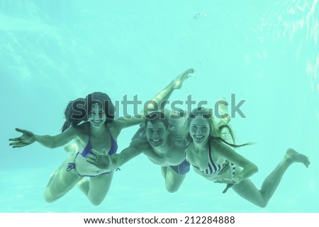 Group of young friends underwater in swimming pool - stock photo