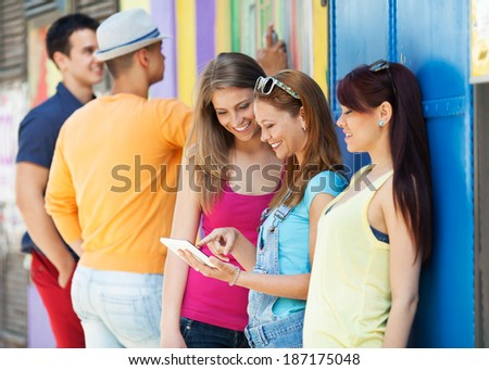 Group of young friends using a digital tablet in the street. - stock photo