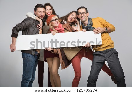 Group of young friends with advert board - stock photo