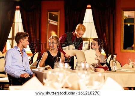 Group of young friends with choosing in a luxury restaurant - stock photo