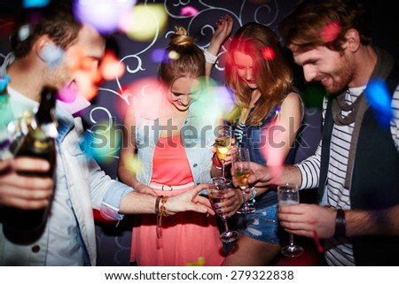 Group of young friends with flutes of champagne having party in club - stock photo