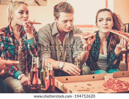 Group of young friends with pizza and bottles of drink celebrating in home interior - stock photo
