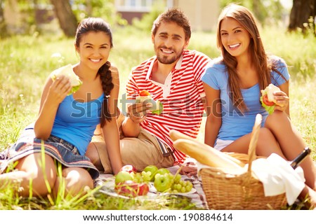 Group of young friends with sandwiches looking at camera at picnic in the country - stock photo