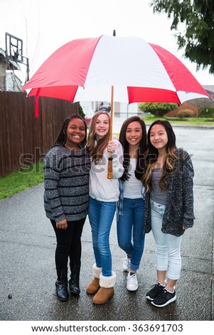 Group of young girl friends holding an umbrella in the rain