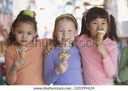Group of young girls eating ice cream cones - stock photo