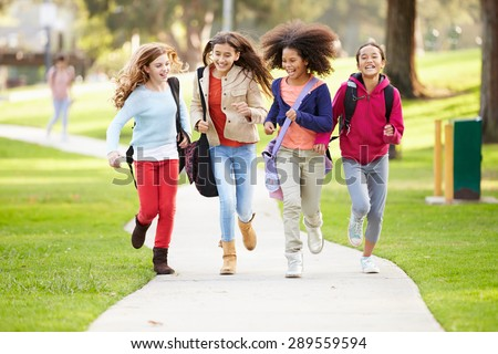 Group Of Young Girls Running Towards Camera In Park - stock photo