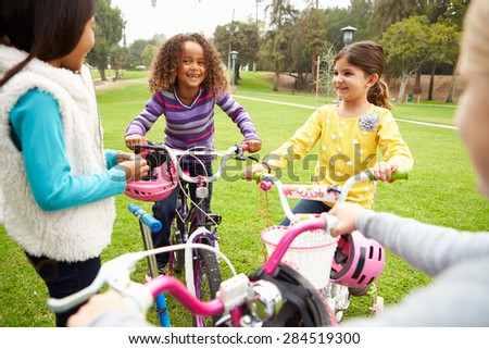 Group Of Young Girls With Bikes In Park