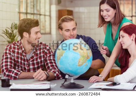 Group of Young Happy Friends Looking at the Globe on Top of the Table - stock photo